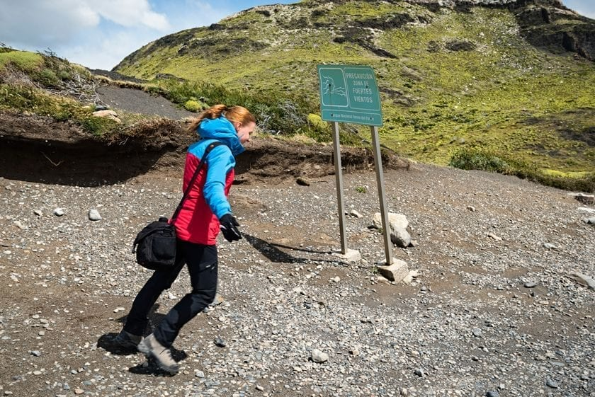 A person posing in a strong wind in Torres del Paine national park in Patagonia.