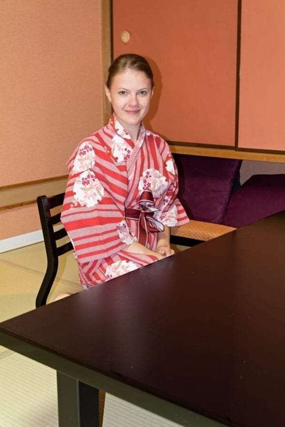 A young lady dressed in a yukata in a traditional ryokan room.
