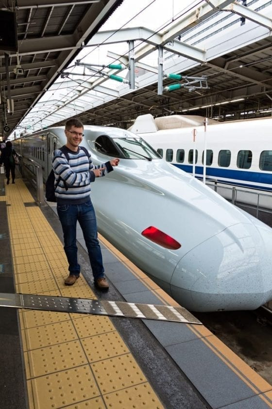 View of a passenger posing in front of a Shinkansen in Osaka station.