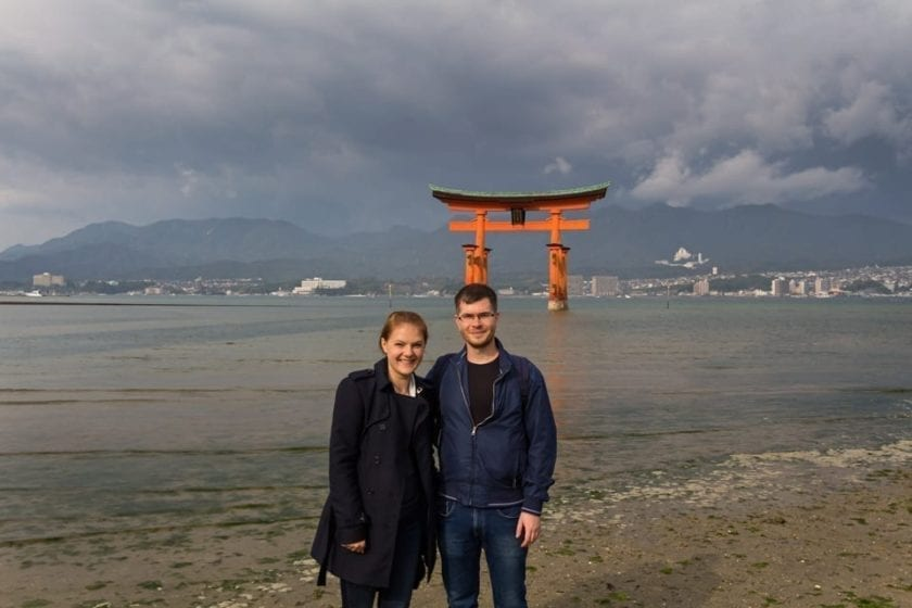 View of a young couple posing in front of the floating torii gate of Itsukushima shrine on Miyajima island.