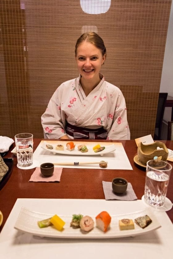 A picture of a young lady dressed in a traditional yukata, enjoying her kaiseki dinner in a ryokan. Kaiseki is a great way to enjoy various samples of famous Japanese food.