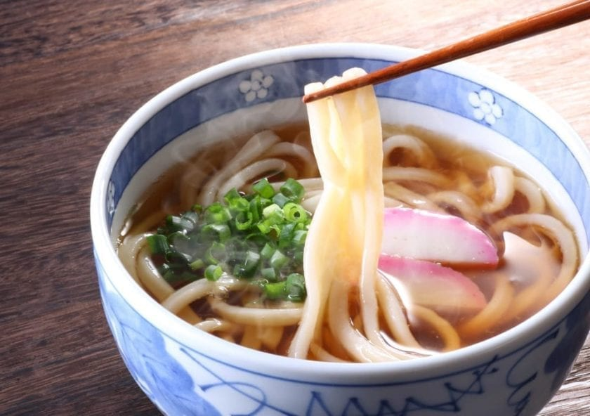 A picture of a bowl of udon noodles in a broth.