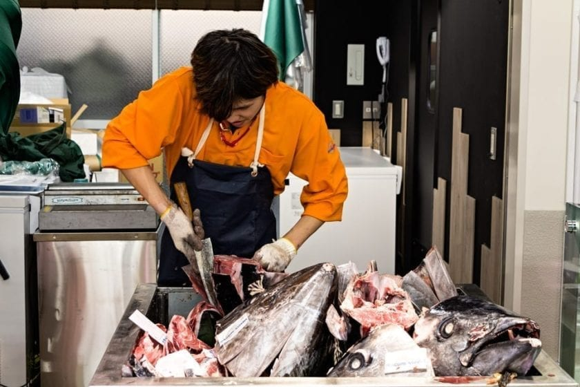 A man cutting Tuna in Tsukiji market in Tokyo - the first activity on our Tokyo 2 day itinerary