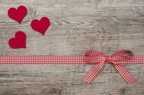 Hearts and a romantic ribbon on a wooden board