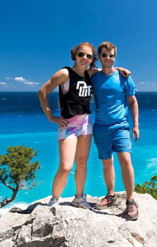 a couple standing on a rock in Sardinia with turquoise Mediterranean sea in the background