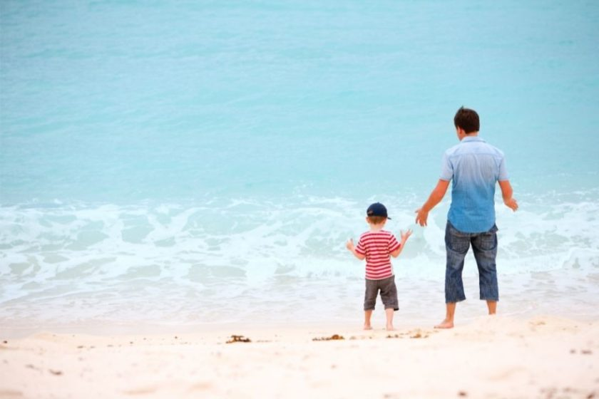 a man and his son enjoying time on the beach